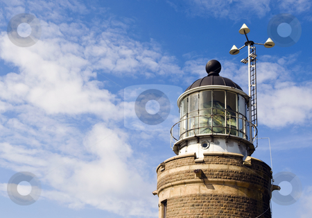 Lighthouse fresnel lamp stock photo, Lighthouse with the fresnel lens housing the lamp and a weather station at day. by Corepics VOF