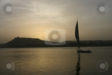 Felucca sailing by at sunset on the Nile in Aswan Egypt stock photo, Felucca sailing by at sunset on the Nile in Egypt by Sharron Schiefelbein