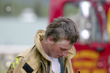 After the fire stock photo, Young fireman tired after the fire is out. by Sharron Schiefelbein
