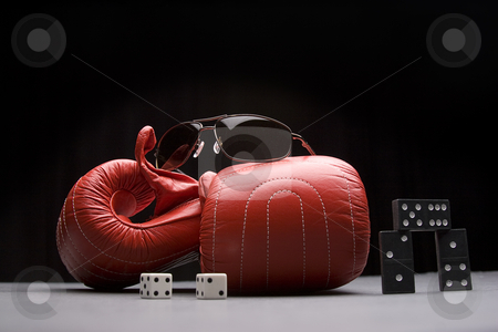 Game of chance and skill stock photo, Men's sunglasses place on top of boxing gloves with a pair of dice rolled on snake eyes and three dominos by Yann Poirier