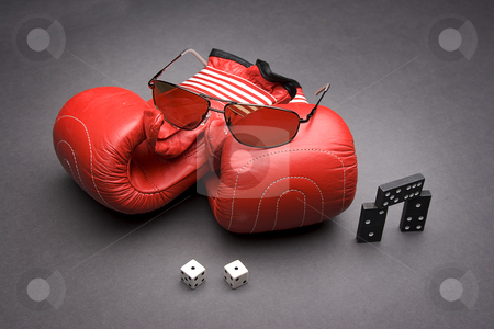 Game of chance and skill stock photo, Men's sunglasses place on top of a pile of dominos with a pair of dice rolled on snake eyes with three dominos by Yann Poirier
