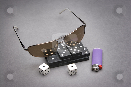 Game of chance stock photo, Men's sunglasses place on top of a pile of dominos with a pair of dice rolled on snake eyes by Yann Poirier
