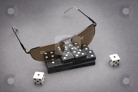 Dominos and snake eye stock photo, Men's sunglasses place on top of a pile of dominos with a pair of dice rolled on snake eyes by Yann Poirier