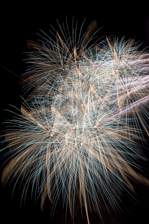 Firework stock photo, Blue and gold firework display trailing in the wind by Yann Poirier