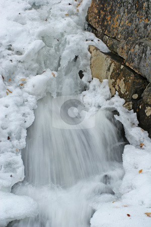 Snow covered stream stock photo, Water falls moving out from under snow pack with rock on side by Marianne Dent