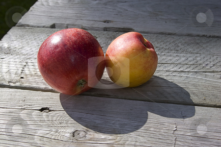 Apple and peach stock photo, An appel and a peach on a wooden picnic table by Yann Poirier