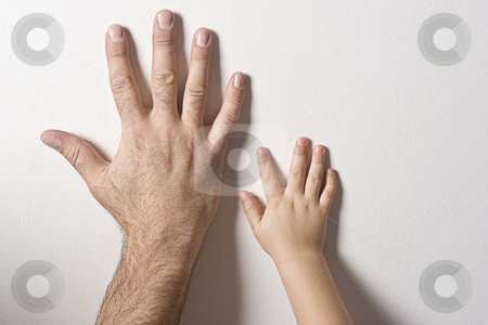 Father and son hands stock photo, Left hand of father and son on a white wall by Yann Poirier