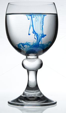 Poisonned water stock photo, Wine glass on white background filled with water and blue colorant representing poison by Yann Poirier