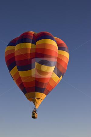 Multi-colored hot air ballon stock photo, Early morning lift off a multi-coloured hot air ballon by Yann Poirier