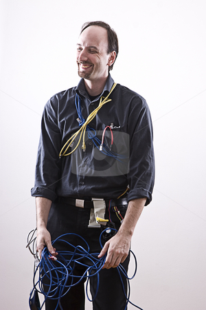 Laughing technician stock photo, Computer technician in full cable gear laughing by Yann Poirier