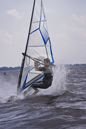 Windsurfer doing a trick stock photo, Windsurfer starting a new trick in the water by Yann Poirier