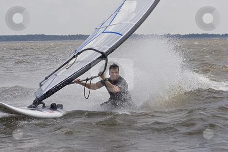 Windsurfer body drag stock photo, Windsurfer doing a body drag trick in the water by Yann Poirier