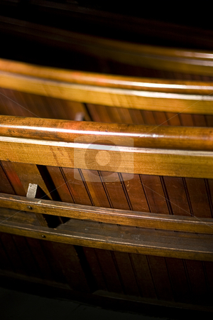 Church wood bench stock photo, Wood bench in dark church partly lighted by the sun by Yann Poirier