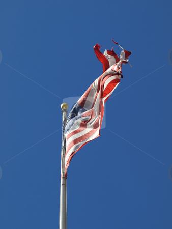 USA flag stock photo, A ripped american flag waving over a blue sky. by Ignacio Gonzalez Prado