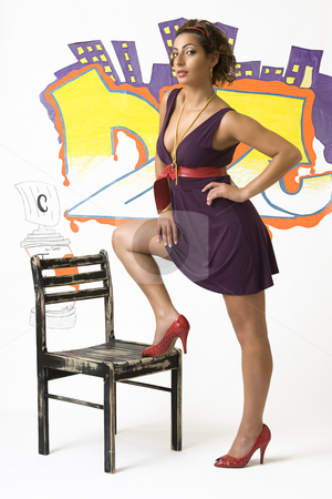 Foot on a chair stock photo, Young women with a foot on a wood chair in front of graffiti by Yann Poirier