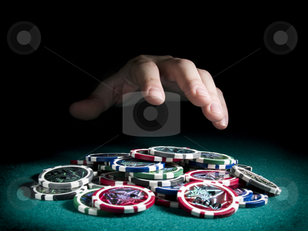 Winning the pot stock photo, A hand about to rake a big pile of chips. by Ignacio Gonzalez Prado