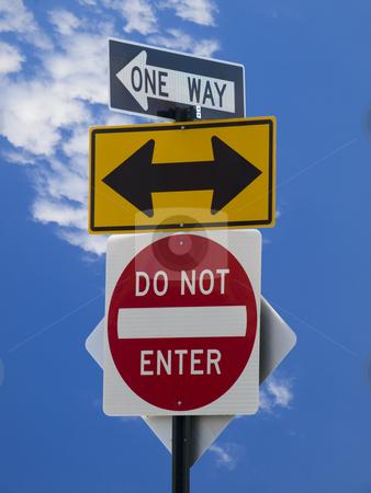 Street signs stock photo, Three street signs over a blue sky with some clouds. by Ignacio Gonzalez Prado
