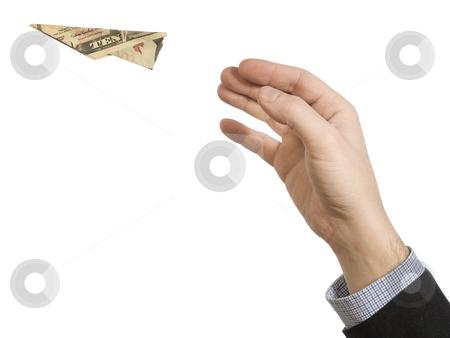 Fly away stock photo, A man's hand throwing a paper plane made of a ten dollar bill. by Ignacio Gonzalez Prado