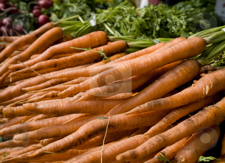 Market groceries stock photo, Several carrots on the foreground and some beets on the background. by Ignacio Gonzalez Prado
