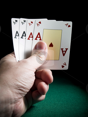 Four aces stock photo, A man's hand holding four aces over a green felt. by Ignacio Gonzalez Prado