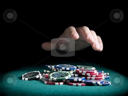 Winning the pot stock photo, A hand about to rake a big pile of chips. by Ignacio Gonzalez Prado