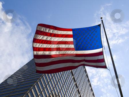 American flag stock photo, American flag waving against a skyscraper and a blue sky. by Ignacio Gonzalez Prado