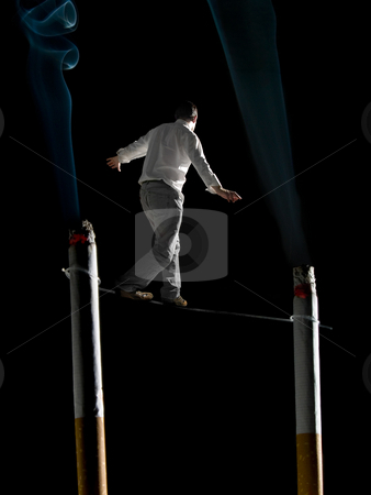 Walking the tightrope of smoking addiction stock photo, A man walking a tightrope suspended  between two big cigarettes. A conceptual image about the health risks of smoking. by Ignacio Gonzalez Prado