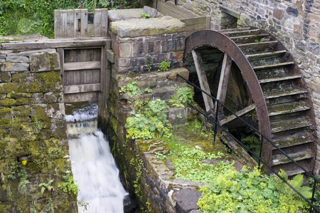 Waterwheel stock photo, Old wooden waterwheel on the side of a mill by Stephen Meese