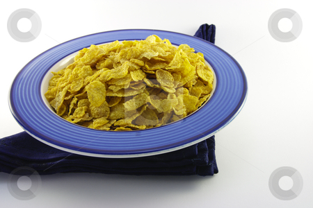 Cornflakes in a Blue Bowl stock photo, Golden crisp cornflakes in a round blue bowl with a black napkin on a white background by Keith Wilson