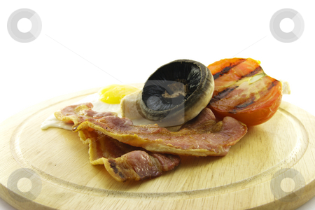 Breakfast on a Wooden Plate stock photo, Slices of crispy pork bacon with half a grilled tomato a fried egg and a grilled mushroomon a wooden round plate with a white background by Keith Wilson