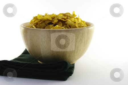 Cornflakes in a Wooden Bowl stock photo, Golden crisp cornflakes in a round wooden bowl with a black napkin on a white background by Keith Wilson