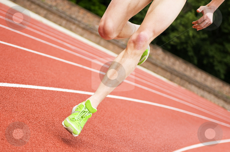 Oval running stock photo, Legs and shoes of a long distance runner on an oval track by Corepics VOF