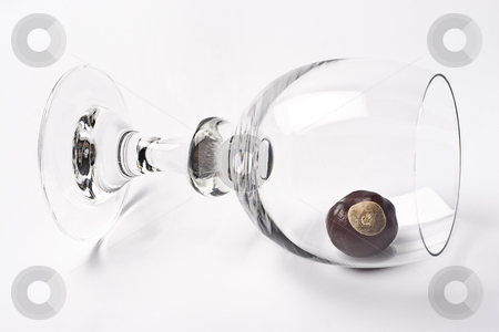 Tippy glass stock photo, Glass of wine tipped over containing one chestnut by Yann Poirier