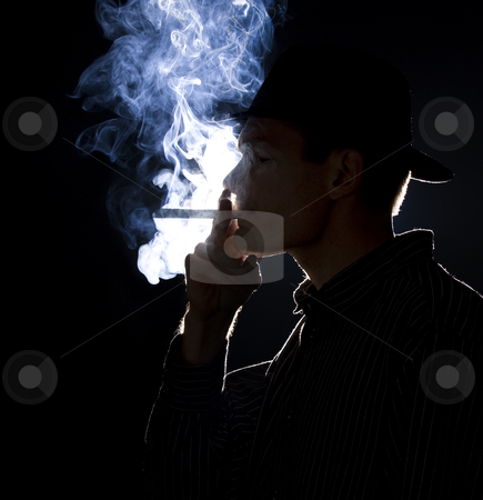 Gangster smoking stock photo, Backlit man smoking a cigar or cigarette with lots of smoke visible by Jandrie Lombard