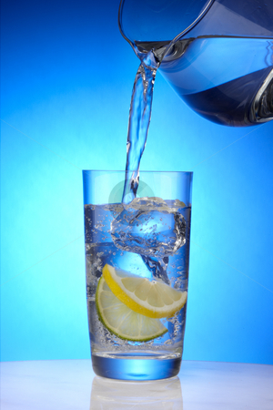 Refreshing glass of water stock photo, Pitcher pours water into a crystal glass with ice, lemon and lime by James Barber