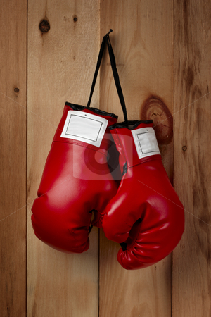 Hangin' em up stock photo, A pair of red boxing gloves hangs from a nail by James Barber