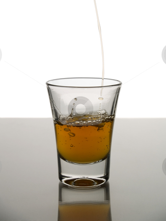 Shot of whisky stock photo, Pouring a shot of whisky on white background over gray floor. by Ignacio Gonzalez Prado