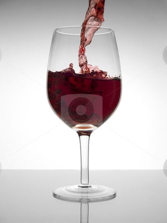 Glass of wine stock photo, A malbec glass being poured with red wine. by Ignacio Gonzalez Prado