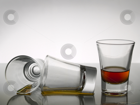 Three shots of whiskey stock photo, Three shots of whiskey on white background over gray floor. by Ignacio Gonzalez Prado
