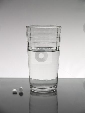 Glass of water stock photo, A glass of water with two pills. by Ignacio Gonzalez Prado