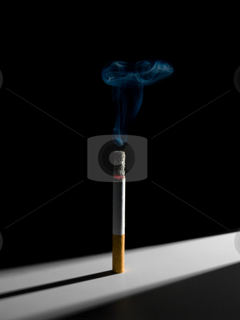 Standing cigarette stock photo, A single smoking cigarette standing in a narrow corridor of light. A conceptual image about the smoking habit. by Ignacio Gonzalez Prado
