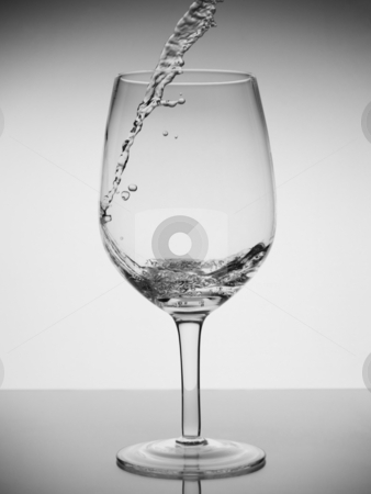 Glass of water stock photo, Water being pored into a glass with reflection on white background. by Ignacio Gonzalez Prado