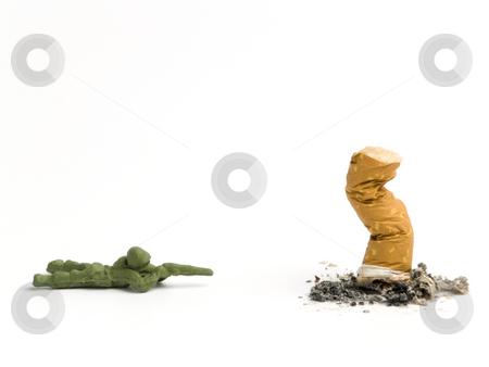 Cigarette stock photo, A toy soldier aiming to a cigarette butt. by Ignacio Gonzalez Prado
