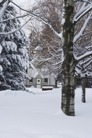 Secret chapel stock photo, Small chapel hidden in the wood, covered with a blanket of snow just after a storm by Yann Poirier
