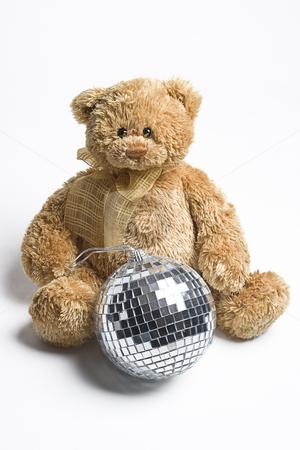 Disco Teddy bear stock photo, Teddy bear sitting on the ground with a disco ball between it's legs by Yann Poirier