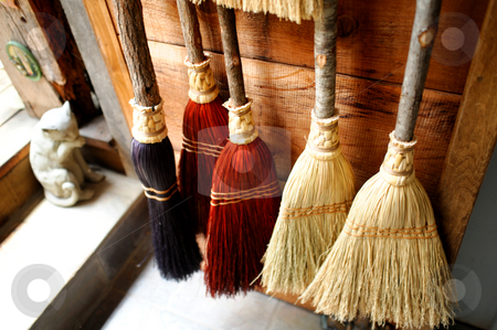 Handmade Brooms stock photo, Old fashioned brooms hanging against a wooden wall by Lynn Bendickson