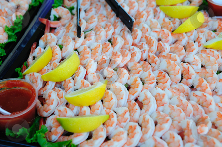 Cooked Shrimp And Lemon Wedges stock photo, A large tray of shelled and cooked shrimp with lemon slices and seafood sauce. by Lynn Bendickson
