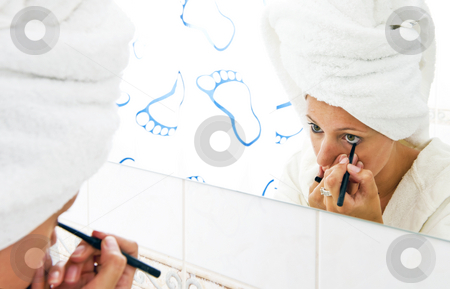 Putting on eye liner stock photo, Young woman with a towel draped around her hair, putting on eye liner in front of the mirror by Corepics VOF