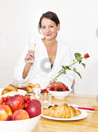 Valentine girl stock photo, Young woman at breakfast holding a glass of champagne and a red rose for her valentine by Corepics VOF