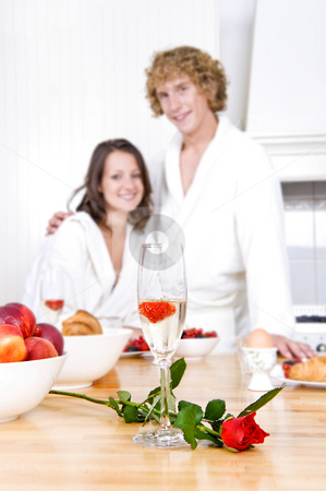 Valentine's attributes stock photo, Glass of champagne with a strawberry floating on it, and a red rose on a breakfast counter with a young couple in the background. by Corepics VOF